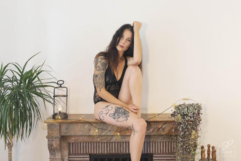 Femme modèle lingerie assise sur cheminée